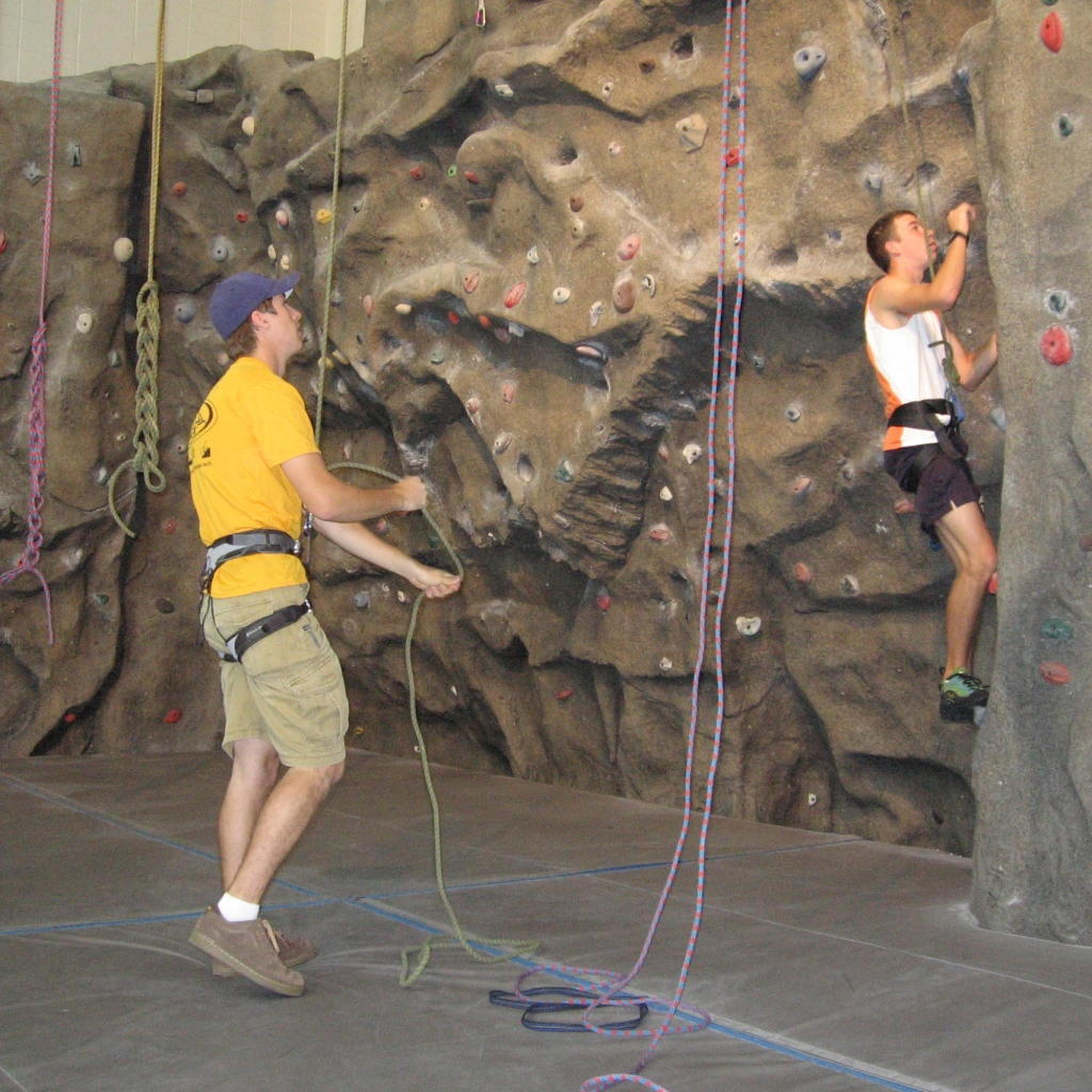 Climbing wall assistant helping a student repell