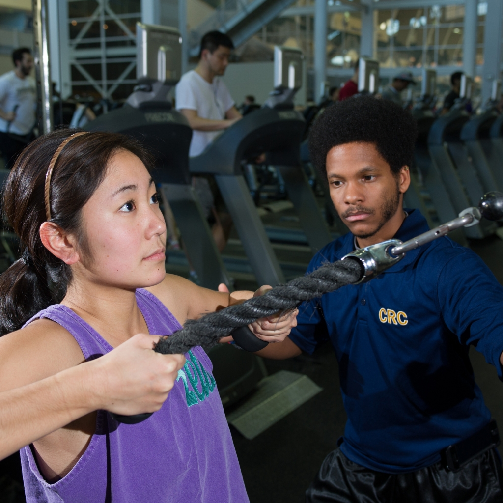 personal trainer helping a student do an exercise
