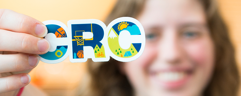 Student staff member hold up a CRC sticker